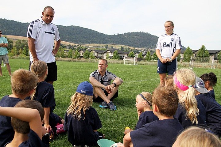 Vancouver Whitecaps captain Jay DeMerit (centre) talks to the children in the Whitecaps soccer camp along with retired Whitecap Carl Valentine and camp coach Becca Kletke Thursday at Marshall Field.